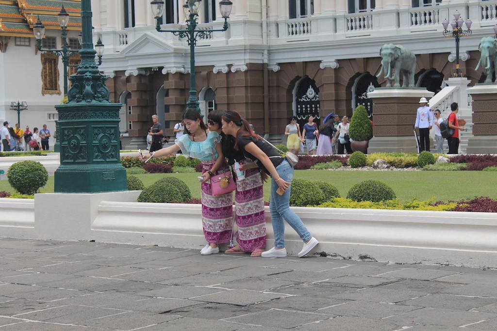 Turistas e tailandesas tiram fotografias m frente ao Palácio Real